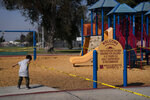 Fernando Olvera, 5, pulls a string of yellow caution tape at a playground closed due to the coronavirus pandemic Thursday, Oct. 1, 2020, in South Central Los Angeles. California's plan to safely reopen its economy will begin to require counties to bring down coronavirus infection rates in disadvantaged communities that have been harder hit by the pandemic. The complex new rules set in place an