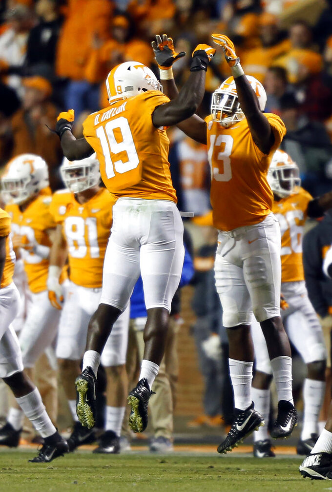 Tennessee linebacker Darrell Taylor (19) celebrates a sack and fumble recovery with teammate linebacker Deandre Johnson (13) in the second half of an NCAA college football game against Kentucky Saturday, Nov. 10, 2018, in Knoxville, Tenn. Tennessee won 24-7. (AP Photo/Wade Payne)