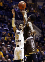 West Virginia guard James Bolden (3) shoots while defended by Lehigh guard Lance Tejada (5) during the second half of an NCAA college basketball game Sunday, Dec. 30, 2018, in Morgantown, W.Va. (AP Photo/Raymond Thompson)