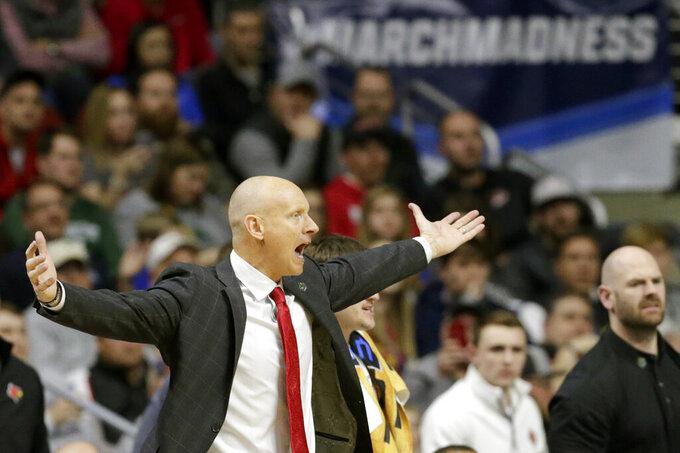 Louisville coach Chris Mack gestures during the second half of a first round men's college basketball game against Minnesota in the NCAA Tournament, in Des Moines, Iowa, Thursday, March 21, 2019. (AP Photo/Nati Harnik)