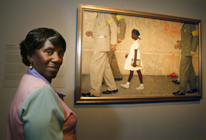 """FILE - In this July 20, 2006, file photo, Lucille Bridges poses next to the original 1964 Norman Rockwell painting, """"The Problem We All Live With,"""" showing her daughter Ruby, inside the Museum of Fine Arts in Houston. Bridges, a Hurricane Katrina evacuee and Houston resident after the storm, looked for the first time at the Rockwell original capturing her oldest daughter, Ruby, as she was escorted by U.S. marshals into an all-white New Orleans school during integration nearly a half-century earlier. New Orleans' mayor announced Tuesday, Nov. 10, 2020, that Lucille Bridges, the mother of civil rights activist Ruby Bridges, had died at the age of 86. (Steve Ueckert/Houston Chronicle via AP, File)"""