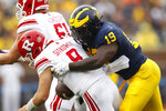 FILE  - In this Saturday, Sept. 28, 2019, file photo, Michigan defensive lineman Kwity Paye (19) sacks Rutgers quarterback Artur Sitkowski (8) in the first half of an NCAA college football game, in Ann Arbor, Mich. Michigan has been good, not great, under coach Jim Harbaugh. Michigan defensive end Kwity Paye said the 19th-ranked team is under the radar and the Wolverines have taken a lot of punches from people, criticizing the relatively underwhelming state of the program. (AP Photo/Paul Sancya, File)