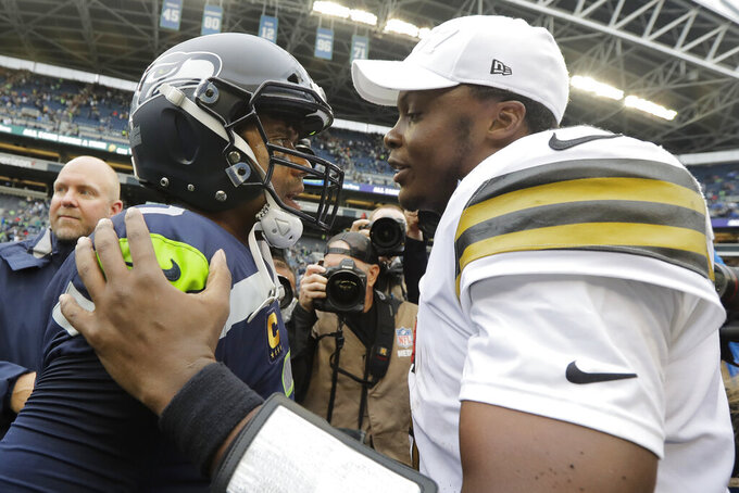 Seattle Seahawks quarterback Russell Wilson, left, talks with New Orleans Saints quarterback Teddy Bridgewater, right, after an NFL football game, Sunday, Sept. 22, 2019, in Seattle. (AP Photo/Ted S. Warren)