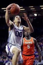 Kansas State's Mike McGuirl (0) gets past Florida A&M's Nasir Core (5) to shoot during the first half of an NCAA college basketball game Monday, Dec. 2, 2019, in Manhattan, Kan. (AP Photo/Charlie Riedel)