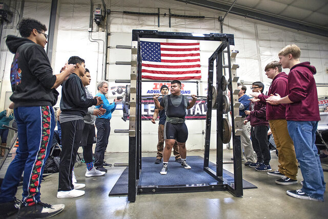 In this Dec. 7, 2019 photo, Jaredval Caguiat, 17, finishes squatting 615 pounds, breaking a state record of 551.2 pounds, during the 19th Annual Ketchikan Winter Powerlifting Competition at Body Mechanics Gym in Ketchikan, Alaska. (Dustin Safranek/Ketchikan Daily News via AP)