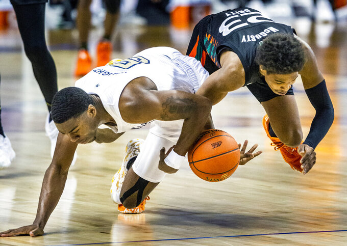 Georgia Tech's Moses Wright, left, and Miami's Elijah Olaniyi scramble for a loose ball during an NCAA college basketball game in the quarterfinal round of the Atlantic Coast Conference tournament in Greensboro, N.C., Thursday, March 11, 2021. (Woody Marshall/News & Record via AP)
