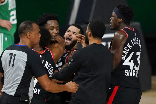 Teammates mob Toronto Raptors' OG Anunoby, second player from left, after Anunoby's game winning shot at the buzzer in the second half of an NBA conference semifinal playoff basketball game against the Boston Celtics Thursday, Sept 3, 2020, in Lake Buena Vista Fla. (AP Photo/Mark J. Terrill)