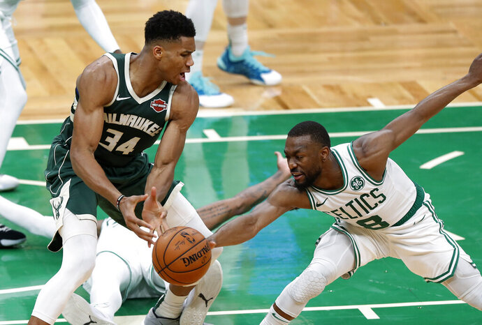 Boston Celtics' Kemba Walker reaches in to knock the ball away from Milwaukee Bucks' Giannis Antetokounmpo during the second quarter of an NBA basketball game Wednesday, Oct. 30, 2019, in Boston. (AP Photo/Winslow Townson)