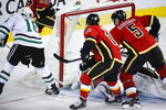 Calgary Flames goalie Cam Talbot, obscured, Derek Ryan, center, and Mark Giordano fail to stop Dallas Stars' Joe Pavelski, left, as he scores during the second period of an NHL hockey game Wednesday, Nov. 13, 2019, in Calgary, Alberta. (Jeff McIntosh/The Canadian Press via AP)
