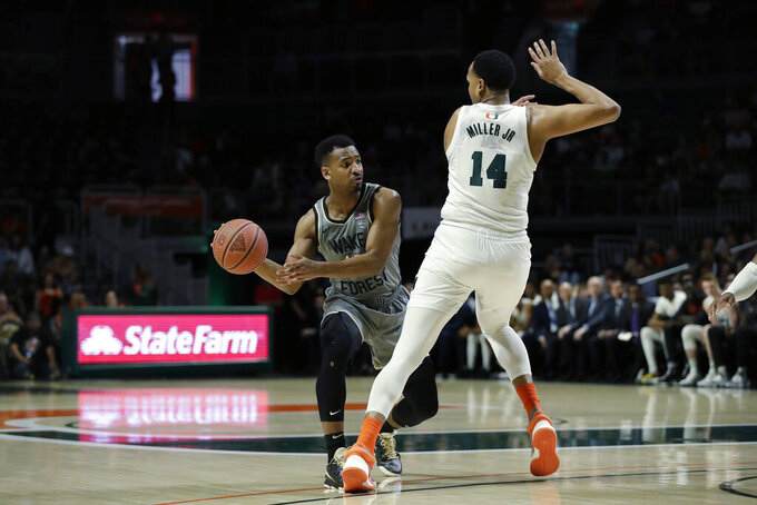 Wake Forest guard Andrien White, left, passes around Miami center Rodney Miller Jr. (14) during the second half of an NCAA college basketball game, Saturday, Feb. 15, 2020, in Coral Gables, Fla. Miami defeated Wake Forest 71-54. (AP Photo/Wilfredo Lee)