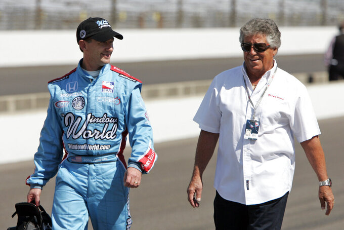 FILE - In this May 10, 2009, file photo, John Andretti, left, walks out of the pit area his his uncle, Mario Andretti, after a practice session on the second day of qualifications for the Indianapolis 500 auto race at the Indianapolis Motor Speedway in Indianapolis. John Andretti, a member of one of racing's most families, has died following a battle with colon cancer, Andretti Autosports announced Wednesday, Jan. 30, 2020. He was 56.  (AP Photo/Darron Cummings, File)