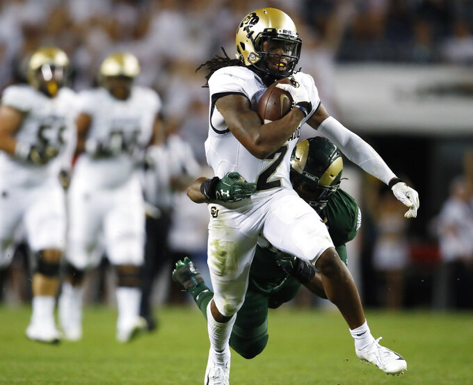 FILE - In this Aug. 31, 2018, file photo, Colorado wide receiver Laviska Shenault Jr., front, is pulled down after a long gain by Colorado State linebacker Josh Watson in the second half of an NCAA college football game, in Denver. Shenault was named to The Associated Press Midseason All-America team, Tuesday, Oct. 16, 2018. (AP Photo/David Zalubowski, File)