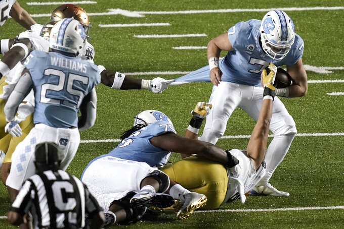 North Carolina quarterback Sam Howell (7) tries to find some running room during the second half of the team's NCAA college football game against Notre Dame in Chapel Hill, N.C., Friday, Nov. 27, 2020. (AP Photo/Gerry Broome)