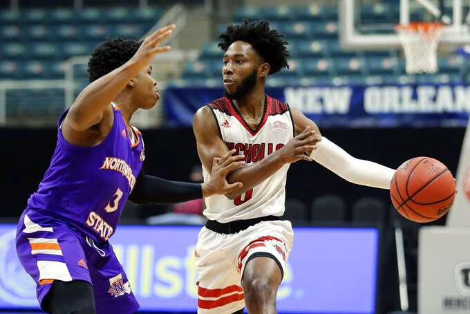 Nicholls State guard Kevin Johnson, right, looks to drive around Northwestern State guard Brian White (3) during the first half of an NCAA college basketball game in the Southland Conference men's tournament semifinals Friday, March 12, 2021, in Katy, Texas. (AP Photo/Michael Wyke)