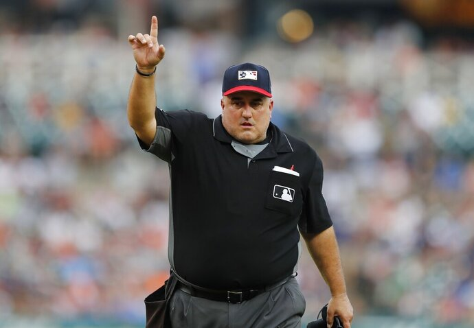 In this July 5, 2019, photo, home plate umpire Eric Cooper signals during the third inning of a baseball game between the Detroit Tigers and the Boston Red Sox in Detroit. Cooper, the Major League Baseball umpire who worked the AL Division Series two weeks ago, has died. He was 52. Commissioner Rob Manfred announced Cooper's death Sunday, Oct. 20. Cooper died after having a blood clot. (AP Photo/Carlos Osorio)