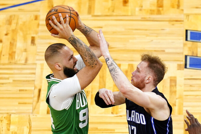 Boston Celtics guard Evan Fournier, left, goes up for a shot against Orlando Magic forward Ignas Brazdeikis during the second half of an NBA basketball game, Wednesday, May 5, 2021, in Orlando, Fla. (AP Photo/John Raoux)