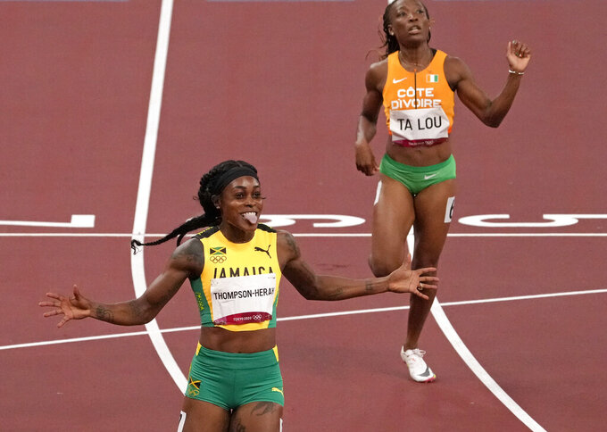 Elaine Thompson-Herah, of Jamaica celebrates after winning the gold medal in the final of the women's 200-meter at the 2020 Summer Olympics, Tuesday, Aug. 3, 2021, in Tokyo, Japan. (AP Photo/Charlie Riedel)