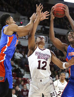 Mississippi State guard Robert Woodard (12) reaches for a rebound between  Florida's KeVaughn Allen, left and Dontay Bassett during the first half of an NCAA college basketball game Tuesday, Jan. 15, 2019, in Starkville, Miss. Mississippi State won 71-68. (AP Photo/Jim Lytle)