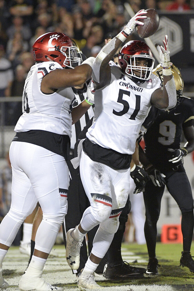 Cincinnati defensive end Kimoni Fitz (51) is congratulated by defensive tackle Cortez Broughton, left, after recovering a fumble in the end zone for a touchdown, following a sack of Central Florida quarterback McKenzie Milton during the first half of an NCAA college football game Saturday, Nov. 17, 2018, in Orlando, Fla. (AP Photo/Phelan M. Ebenhack)