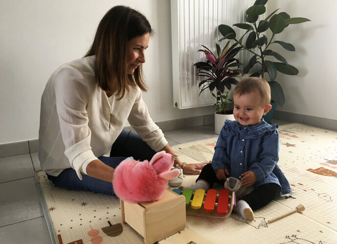 Sandrine Rudnicki, a 38 years old single woman smiles to her 10-month old daughter Emilia who was conceived through in-vitro fertilization, Monday Oct.14, 2019 in Saint-Pryve-Saint-Mesmin, near Orleans, France. France's lower house of parliament is set to adopt a bill that would give single women and lesbian couples access to in-vitro fertilization and related procedures. (AP Photo/Catherine Gaschka)