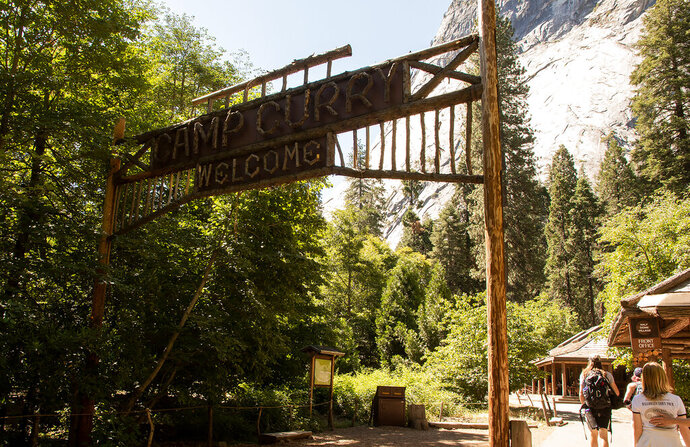 This Monday, July 15, 2019, photo released by the National Park Service shows a Camp Curry welcome sign in Yosemite National Park, Calif. On Monday, July 15, 2019, Delaware North, a company that lost its contract to run Yosemite National Park's hotels, restaurants and outdoor activities, has settled a lawsuit with the National Park Service and the park's new concession operator over rights to the names of famous park landmarks. (National Park Service via AP)