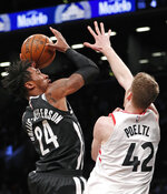 Toronto Raptors center Jakob Poeltl (42) defends as Brooklyn Nets forward Rondae Hollis-Jefferson (24) shoots during the second half of an NBA basketball game, Tuesday, March 13, 2018, in New York. The Raptors defeated the Nets 116-102. (AP Photo/Kathy Willens)