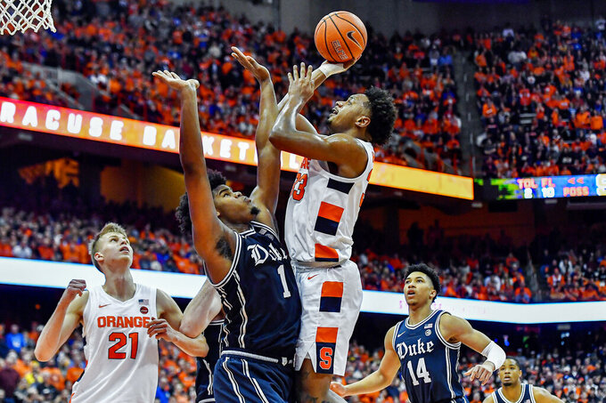 FILE - In this Feb. 1, 2020, file photo, Syracuse forward Elijah Hughes, right, shoots over Duke center Vernon Carey Jr. during the second half of an NCAA college basketball game in Syracuse, N.Y. Hughes was selected to the Associated Press All-ACC team selected Tuesday, March 10, 2020. (AP Photo/Adrian Kraus, File)