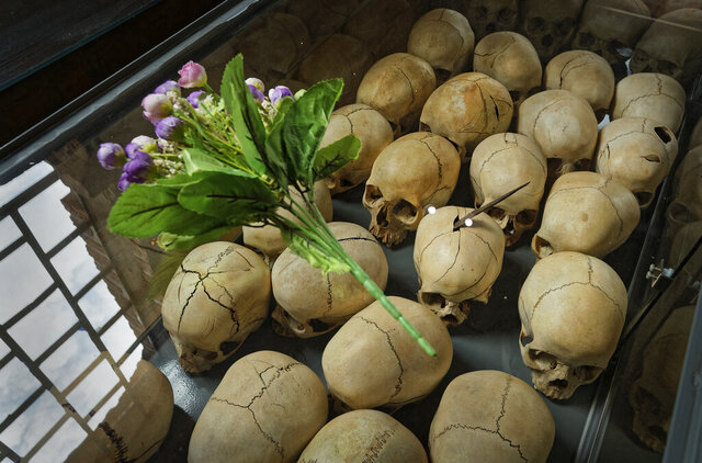 FILE- In this April 5, 2019 file photo, flowers are laid on top of a glass case containing the skulls of some of those who were slaughtered as they sought refuge in the church, kept as a memorial to the thousands who were killed in and around the Catholic church during the 1994 genocide, inside the church in Ntarama, Rwanda. A valley dam that authorities in Rwanda say could contain about 30,000 bodies has been discovered more than a quarter-century after the country's genocide in which 800,000 ethnic Tutsi and Hutus who tried to protect them were killed. Rwanda on Tuesday marks the 26th anniversary of the genocide. (AP Photo/Ben Curtis, File)