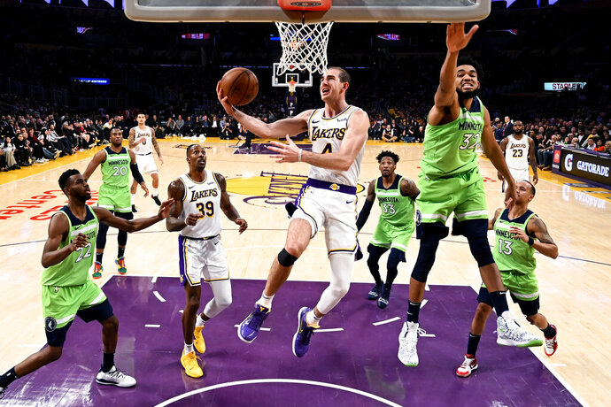 FILE - In this Dec. 8, 2019, file photo, Los Angeles Lakers' Alex Caruso (4) goes to basket under pressure from Minnesota Timberwolves' Karl-Anthony Towns (32) during the second half of an NBA basketball game in Los Angeles. Caruso was averaging 5.4 points, 1.9 rebounds and 1.8 assists in 17.8 minutes wen the hiatus began. With Avery Bradley opting out of the restart and Rajon Rondo breaking his thumb in practice this month, the 6-foot-5 Caruso should have a greater role in the Lakers' bench during the restart. (AP Photo/Ringo H.W. Chiu, File)