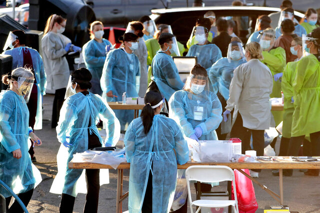 Medical personnel prepare to test hundreds of people lined up in vehicles Saturday, June 27, 2020, in Phoenix's western neighborhood of Maryvalefor free COVID-19 tests organized by Equality Health Foundation, which focuses on care in underserved communities. As coronavirus infections explode in states like Arizona and Florida, people in communities of color are fighting to get tested. Public health experts say wider testing helps people in underserved neighborhoods and is key to controlling a pandemic. (AP Photo/Matt York)