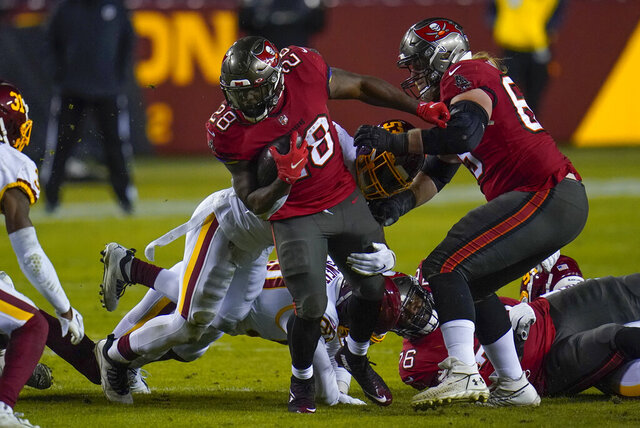 Tampa Bay Buccaneers running back Leonard Fournette (28) is taken down by Washington Football Team middle linebacker Jon Bostic (53) during the first half of an NFL wild-card playoff football game, Saturday, Jan. 9, 2021, in Landover, Md. (AP Photo/Julio Cortez)