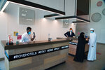 FILE - In this July 6, 2020  file photo, the front desk staff wearing masks due to the coronavirus pandemic help customers at the Rove City Centre Hotel in Dubai, United Arab Emirates. Hundreds of thousands of foreign residents of the UAE are struggling to return to the country after a lockdown over the coronavirus. Dubai opening to tourists helped some return, as Westerners and those from the Gulf Cooperation Council states get visas on arrival in the UAE. But others, including those from the Asian nations that supply the Emirates its army of laborers, cleaners, taxi drivers and office workers, need a visa issued beforehand. (AP Photo/Jon Gambrell, File)