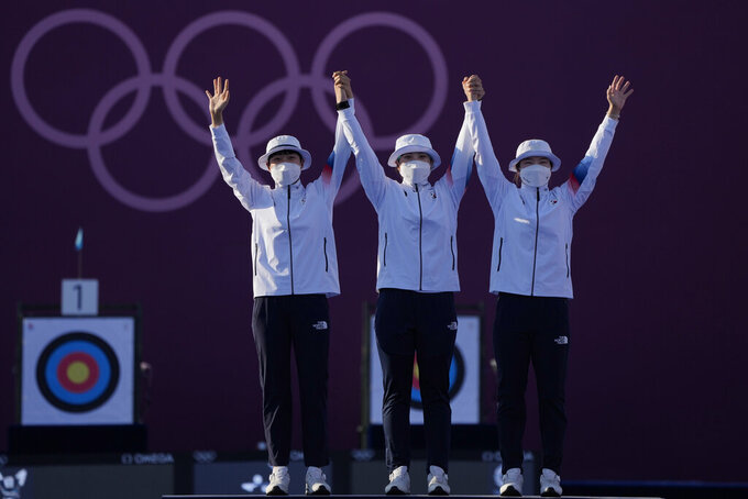 From left first placed South Korea's An San, Jang Minhee, and Kang Chaeyoung celebrate on the podium during the medal ceremony of the women's team competition at the 2020 Summer Olympics, Sunday, July 25, 2021, in Tokyo, Japan. (AP Photo/Alessandra Tarantino)