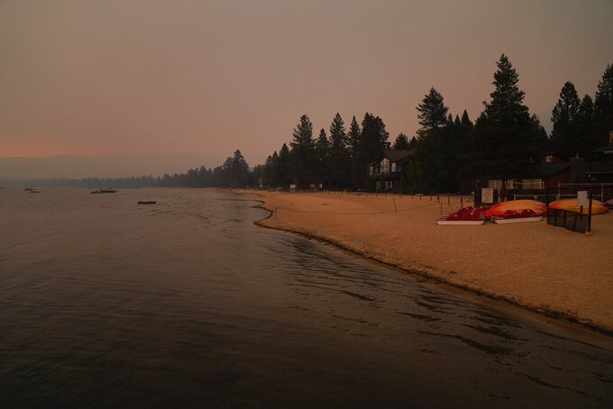 FILE - In this Tuesday, Aug. 31, 2021 file photo, an empty beach is seen after a mandatory evacuation was ordered due to the Caldor Fire in South Lake Tahoe, Calif. A huge firefighting force gathered Tuesday to defend Lake Tahoe from the wildfire that forced the evacuation of California communities on the south end of the alpine resort and put others across the state line in Nevada on notice to be ready to flee. (AP Photo/Jae C. Hong)
