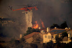 A helicopter drops water while battling the Saddleridge fire in Porter Ranch, Calif., on Friday, Oct. 11, 2019. (AP Photo/Noah Berger)