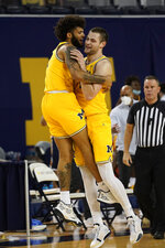 Michigan forward Isaiah Livers, left, and Michigan center Hunter Dickinson celebrate in the first half of an NCAA college basketball game against Toledo in Ann Arbor, Mich., Wednesday, Dec. 9, 2020. (AP Photo/Paul Sancya)