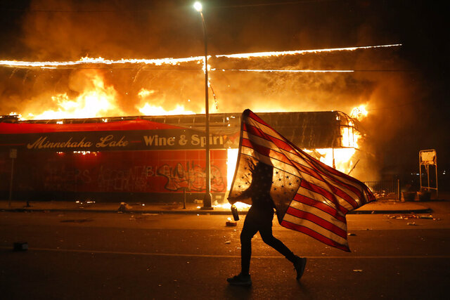 A protester carries a U.S. flag upside, a sign of distress, next to a burning building Thursday, May 28, 2020, in Minneapolis. Protests over the death of George Floyd, a black man who died in police custody Monday, broke out in Minneapolis for a third straight night. (AP Photo/Julio Cortez)