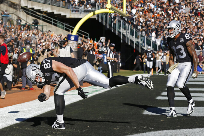Oakland Raiders tight end Foster Moreau (87) celebrates after scoring a touchdown as tight end Darren Waller (83) looks on during the first half of an NFL football game against the Cincinnati Bengals in Oakland, Calif., Sunday, Nov. 17, 2019. (AP Photo/D. Ross Cameron)