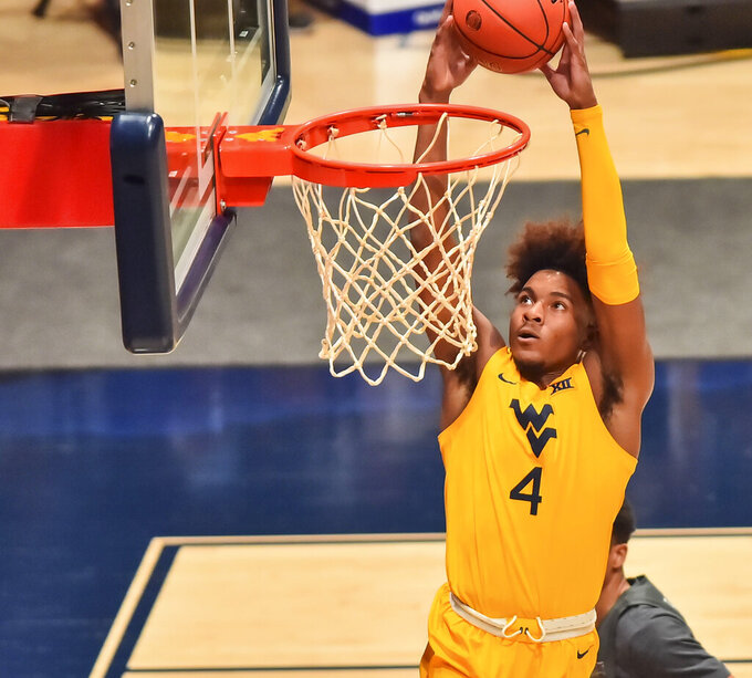 West Virginia guard Miles McBride (4) dunks the ball against Iowa State during the first half of an NCAA college basketball game in Morgantown, W.V., Friday, Dec. 18, 2020. (William Wotring/The Dominion-Post via AP)