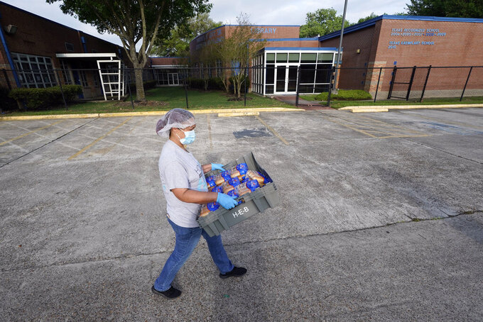 A Houston Independent School District Nutrition Services employee carries packages of buns to be distributed Monday, April 6, 2020, in Houston. HISD relaunched their food distribution efforts throughout the district Monday, with a streamlined process that will implement increased safety measures. (AP Photo/David J. Phillip)