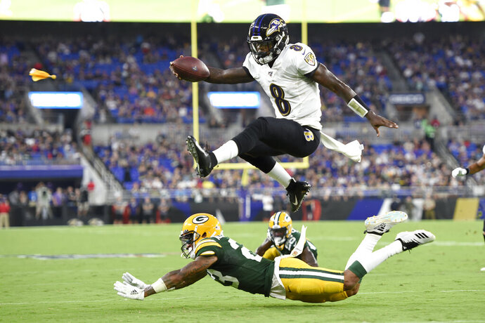 FILE - In this Aug. 15, 2019, file photo, Baltimore Ravens quarterback Lamar Jackson (8) leaps over Green Bay Packers cornerback Jaire Alexander (23) during the first half of a NFL football preseason game in Baltimore.  The Ravens won last year with defense and behind the arm, and mostly legs, of rookie quarterback Lamar Jackson. (AP Photo/Gail Burton, File)