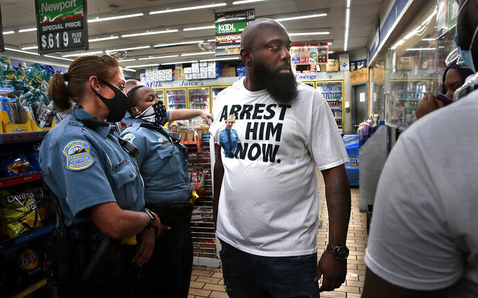 Michael Brown, Sr. arrives at the Ferguson Market as Ferguson police officers talk with protesters who tried to shut down the store on Thursday, July 30, 2020 in Ferguson, Mo.  St. Louis County's prosecutor announced Thursday that he will not charge the former police officer who fatally shot Michael Brown in Ferguson. (Robert Cohen/St. Louis Post-Dispatch via AP)