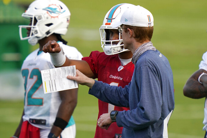 Miami Dolphins quarterback Tua Tagovailoa, center, talks with quarterbacks coach Robby Brown, right, during practice at the NFL football team's training facility Tuesday, Sept. 22, 2020, in Davie, Fla. (AP Photo/Lynne Sladky)