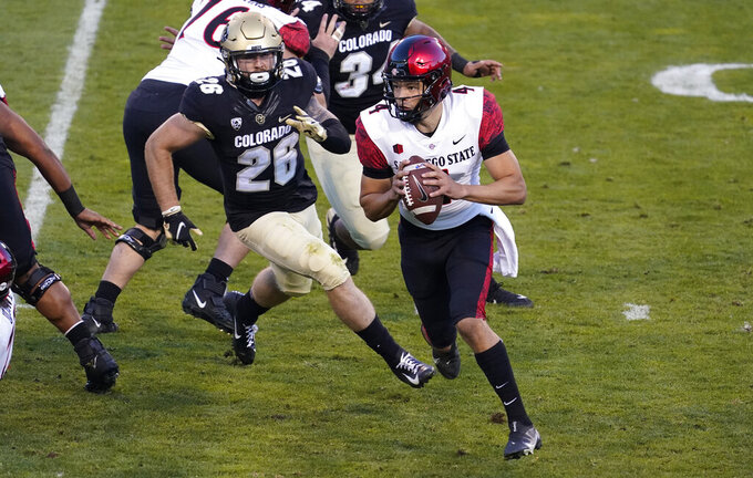 Colorado linebacker Carson Wells, left, pursues San Diego State quarterback Jordon Brookshire, who runs out of the pocket during the first half of an NCAA college football game Saturday, Nov. 28, 2020, in Boulder, Colo. (AP Photo/David Zalubowski)