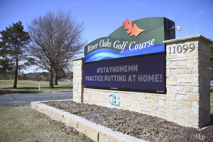 The River Oaks Golf Course marquee lets golfers know where it stands in the effort to help stop the spread of the coronavirus in Minnesota Wednesday, April 1, 2020 near Cottage Grove, Minn. The new coronavirus causes mild or moderate symptoms for most people, but for some, especially older adults and people with existing health problems, it can cause more severe illness or death. (AP Photo/Jim Mone)