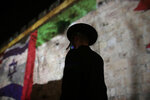 An ultra-Orthodox Jewish man walks past representations of the Israeli, Emirati and Bahraini flags projected onto a wall of Jerusalem's Old City, marking the day of a signing ceremony in Washington signifying the two Gulf nations' normalization of relations with Israel, Tuesday, Sept. 15, 2020. (AP Photo/Maya Alleruzzo)