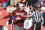 Virginia Tech head coach Justin Fuente, left, disputes a call with an official during the first half of an NCAA college football game against Virginia in Charlottesville, Va., Friday, Nov. 29, 2019. (AP Photo/Steve Helber)