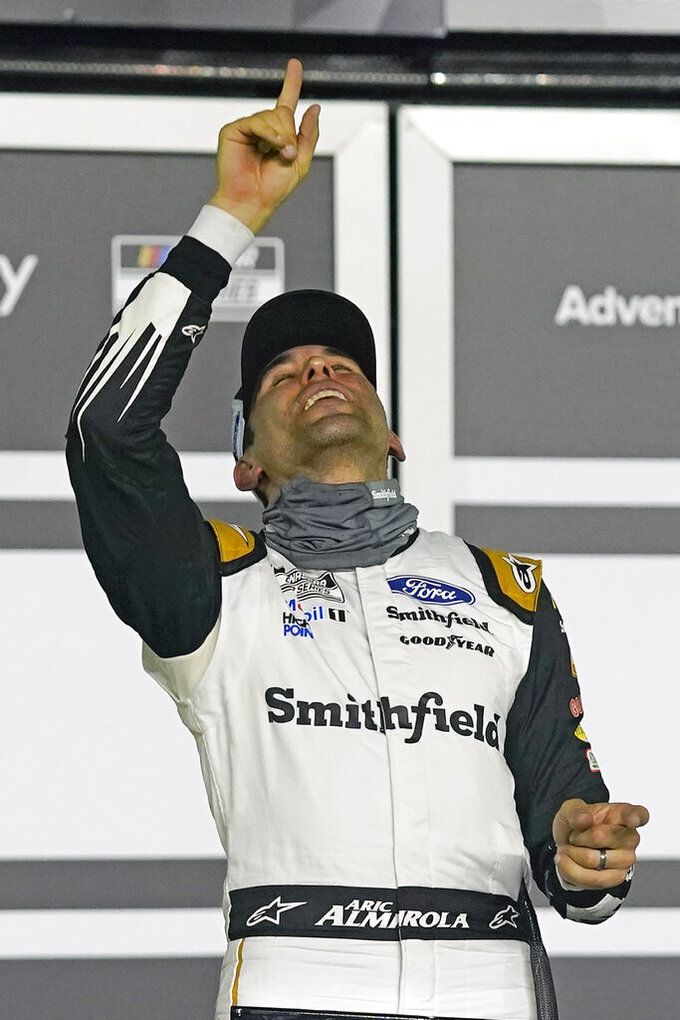 Aric Almirola points upward as he celebrates in Victory Lane after winning the first of two qualifying auto races for the NASCAR Daytona 500 at Daytona International Speedway, Thursday, Feb. 11, 2021, in Daytona Beach, Fla. (AP Photo/John Raoux)