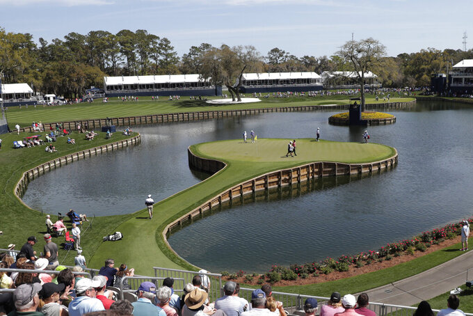 Cameron Champ, Nate Lashley, Kevin Tway and their caddies, walk the 17th green, during the first round of The Players Championship golf tournament Thursday, March 12, 2020 in Ponte Vedra Beach, Fla. (AP Photo/Lynne Sladky)
