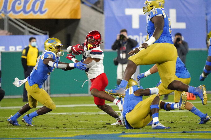 Arizona running back Michael Wiley, second from left, runs next to UCLA defensive back Elisha Guidry (30) during the first half of an NCAA college football game Saturday, Nov. 28, 2020, in Pasadena, Calif. (AP Photo/Marcio Jose Sanchez)